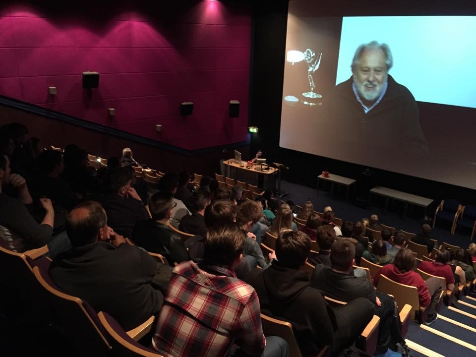 Lord Puttnam lecturing on-screen to students at The University of Sunderland